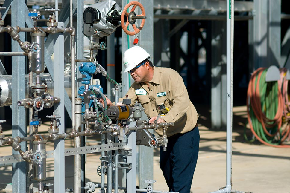 Operator wearing safety gear checking valves and gauges on a hydrogen plant