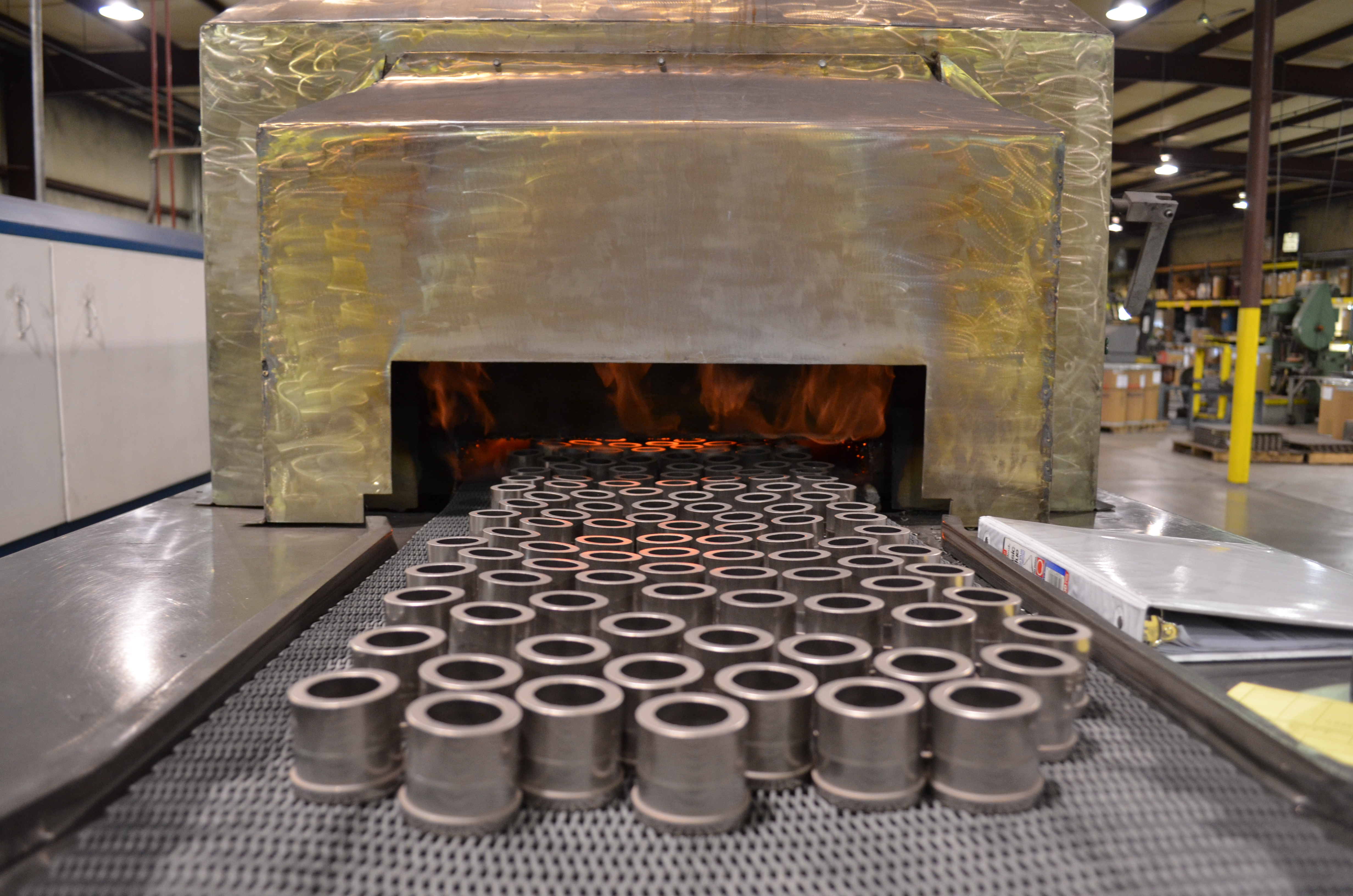 Carbon steel powdered metal parts entering a sintering furnace